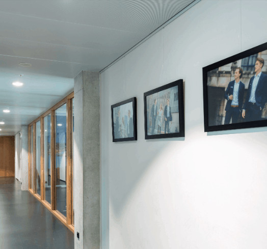 Picture rails allow easy changing of photos of new employees on display in a public area.