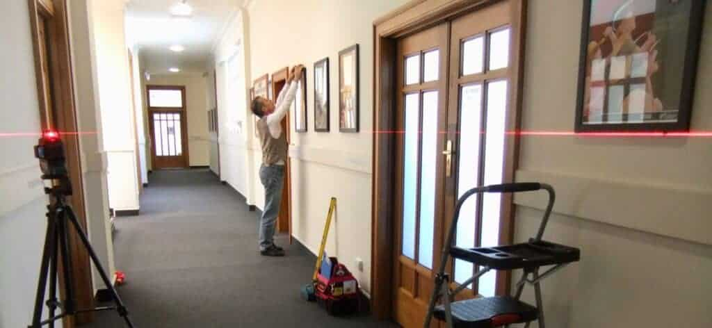 Using a laser level in long hallways is best practice for a long row of identical picture frames.